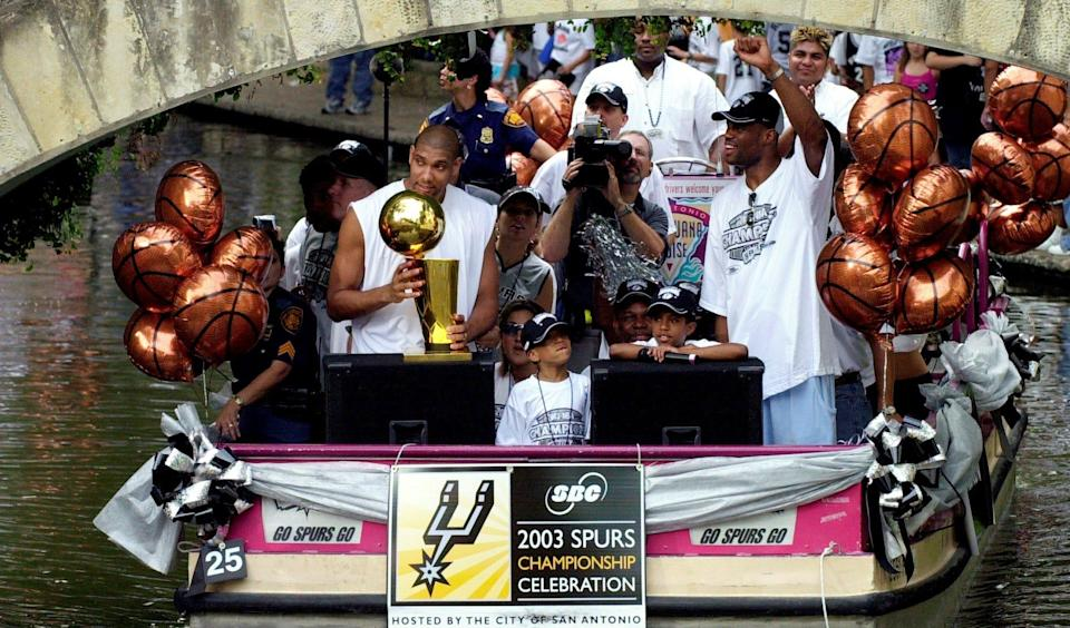 San Antonio Spurs forward Tim Duncan, left, and center David Robinson, right, respond to the crowd as they ride a barge during a  parade to celebrate their NBA championship win, along the San Antonio River in downtown San Antonio.