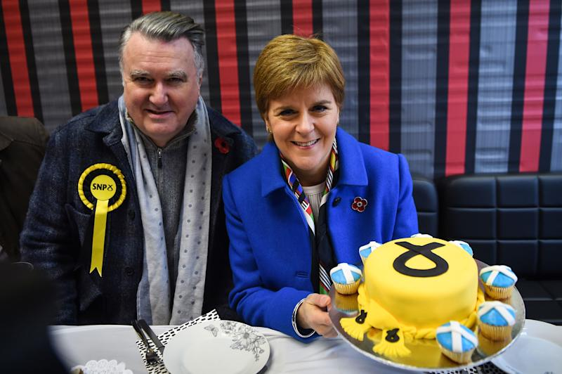 Scottish Nationalist Party (SNP) leader Nicola Sturgeon (R), and Ochil & South Perthshire candidate John Nicolson (L) pose for a photograph with an SNP decorated cake at a Syrian bakery in Alloa, Scotland on November 6, 2019, during campaigning at the start of the General Election campaign. - The splintered country is entering its third general election in four years to try and resolve the crisis launched by voters' decision in 2016 to break away from the European Union after nearly 50 years. (Photo by Andy Buchanan / AFP) (Photo by ANDY BUCHANAN/AFP via Getty Images)
