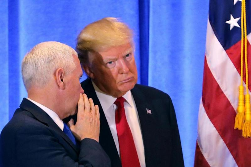 Vice President Mike Pence whispers in the President's ear (Getty)