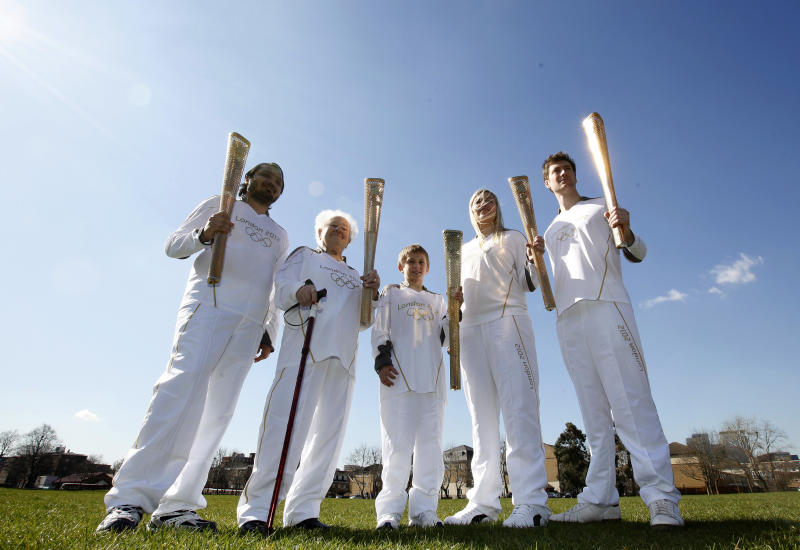 A selection of relay runners including the youngest and the oldest London 2012 Olympic torch relay runners Dominic John MacGowan, centre, aged 11, from Birmingham, England, and Dinah Gould, second left, aged 99, (she will be 100 on May 23) from Harrow, London each hold a torch as they pose for the media on the day that the relay runners are announced along with the uniform that they will wear in a park in east London, Monday, March, 19, 2012. The others are Abul Kasam , left from Tower Hamlets in london, Rosy Ryan from Dumfries, Scotland and Aidan Kirkwood from Newcastle upon Tyne, England. (AP Photo/Alastair Grant)