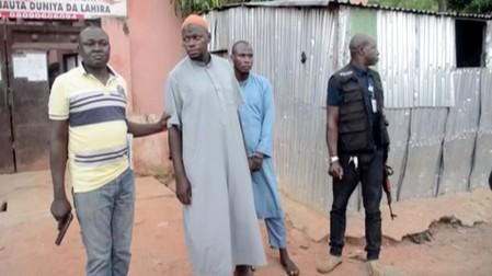 Police officers stand with detained islamic teachers in the northern city of Kaduna