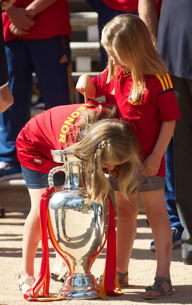 MADRID, SPAIN - JULY 02: Princess Leonor of Spain (L) reaches into the UEFA EURO 2012 trophy while Princess Sofia of Spain watches as King Juan Carlos I of Spain receives players of Spain's victorious national football team at Zarzuela Palace on July 2, 2012 in Madrid, Spain. (Photo by Pool/Getty Images)