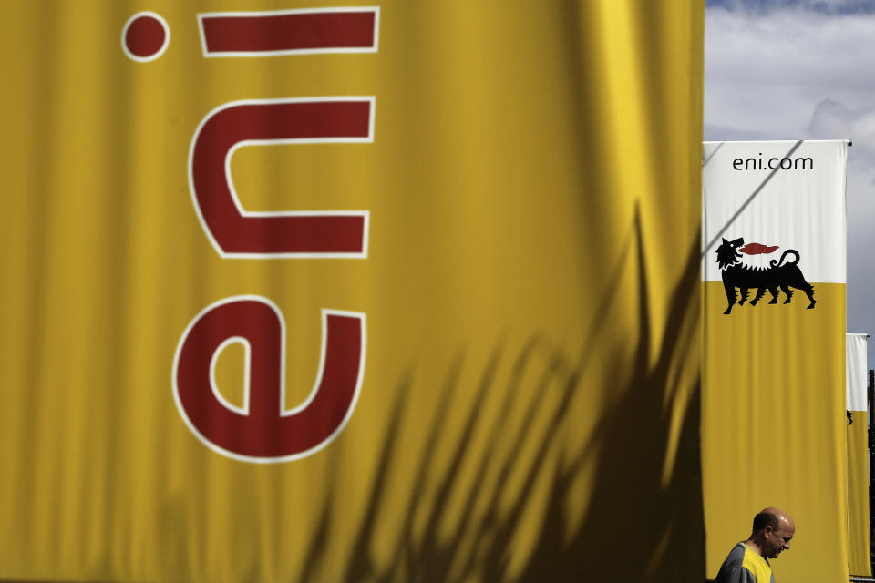 FILE - In this Friday, Feb. 23, 2018 file photo, an employee walks by banners with name and sign of energy firm Eni at Strovolos area in capital Nicosia, Cyprus. Oil giants Shell and Italy's Eni were acquitted Wednesday, March 17, 2021 of corruption charges in a $1.1 billion bribery case involving control of a lucrative oil block on Nigeria. In addition the companies, Eni's current CEO, his predecessor and a former Nigerian oil minister were among 13 defendants acquitted in the three-year-old trial, involving the 2011 purchase of the OPL245 block. (AP Photo/Petros Karadjias, File)