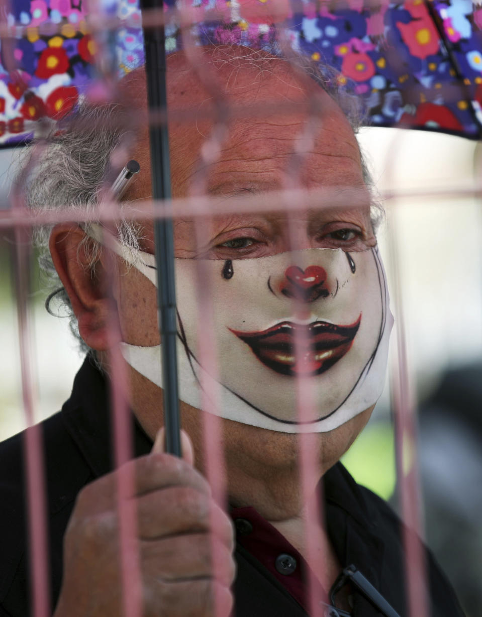An elderly man with a mask painted as a clown, to curb the spread of the new coronavirus waits in line for his dose of the Sinovac Biotech COVID-19 vaccine at the Americas sports center in Ecatepec, a borough on the outskirts of Mexico City, Tuesday, Feb. 23, 2021. (Foto AP/Marco Ugarte