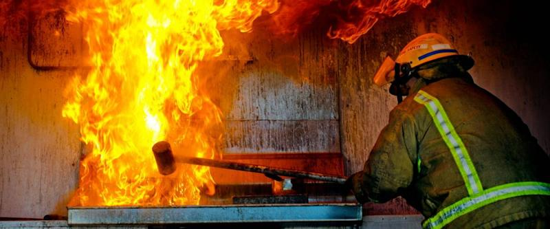 MANGONUI, NZ - APR 06:Firefighter demonstrates how to put out a fire that broke out in the kitchen