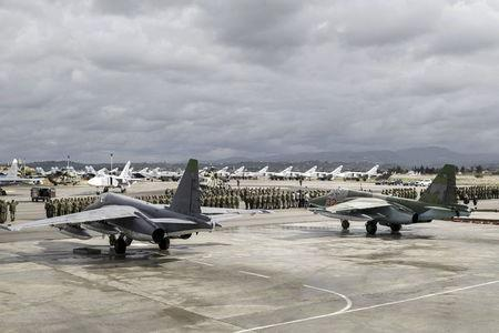 Russian and Syrian servicemen line up near military jets during a ceremony dedicated to the withdrawal of Russian troops from Syria at Hmeymim airbase, Syria, in this March 15, 2016 file photo. REUTERS/Russian Ministry of Defence/Vadim Grishankin/Handout via Reuters/Files