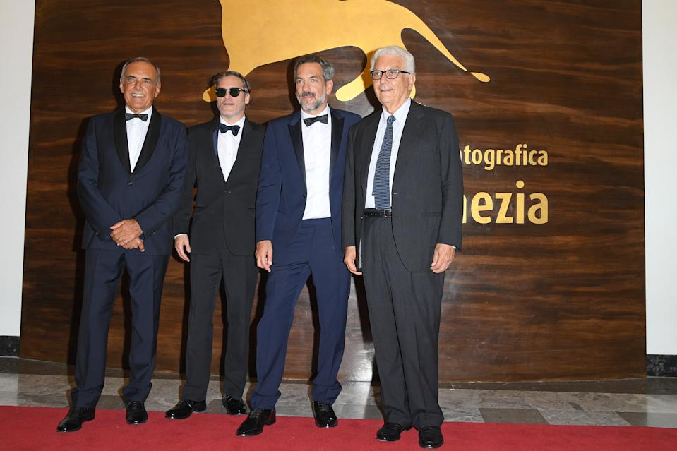 """VENICE, ITALY - AUGUST 31: Drector of the festival Alberto Barbera, Joaquin Phoenix, director Todd Phillips and president of the festival Paolo Baratta walk the red carpet ahead of the """"Joker"""" screening during the 76th Venice Film Festival at Sala Grande on August 31, 2019 in Venice, Italy. (Photo by Daniele Venturelli/WireImage)"""