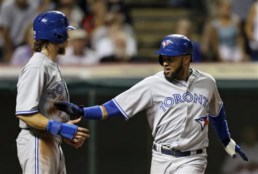 Toronto Blue Jays' Emilio Bonifacio, right, celebrates with Colby Rasmus after both scored on a single by Munenori Kawasaki in the ninth inning of a baseball game against the Cleveland Indians on Wednesday, July 10, 2013, in Cleveland. The Blue Jays held on to win 5-4. (AP Photo/Mark Duncan)