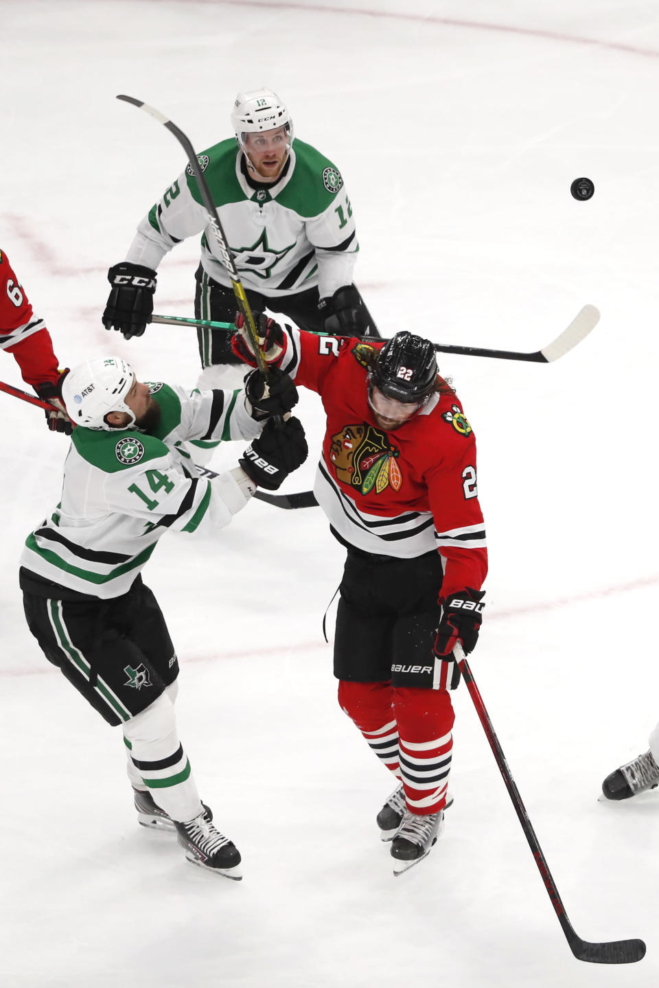 Dallas Stars left wing Jamie Benn (14) and Chicago Blackhawks center Ryan Carpenter (22) battle for the puck during the second period of an NHL hockey game Tuesday, April 6, 2021, in Chicago. (AP Photo/Jeff Haynes)