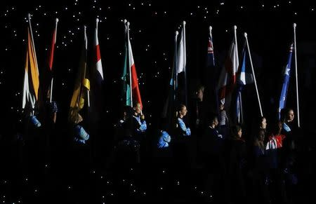 Gold Coast 2018 Commonwealth Games - Closing Ceremony - Carrara Stadium - Gold Coast, Australia - April 15, 2018. Volunteers carry the national flags during the closing ceremony. REUTERS/David Gray