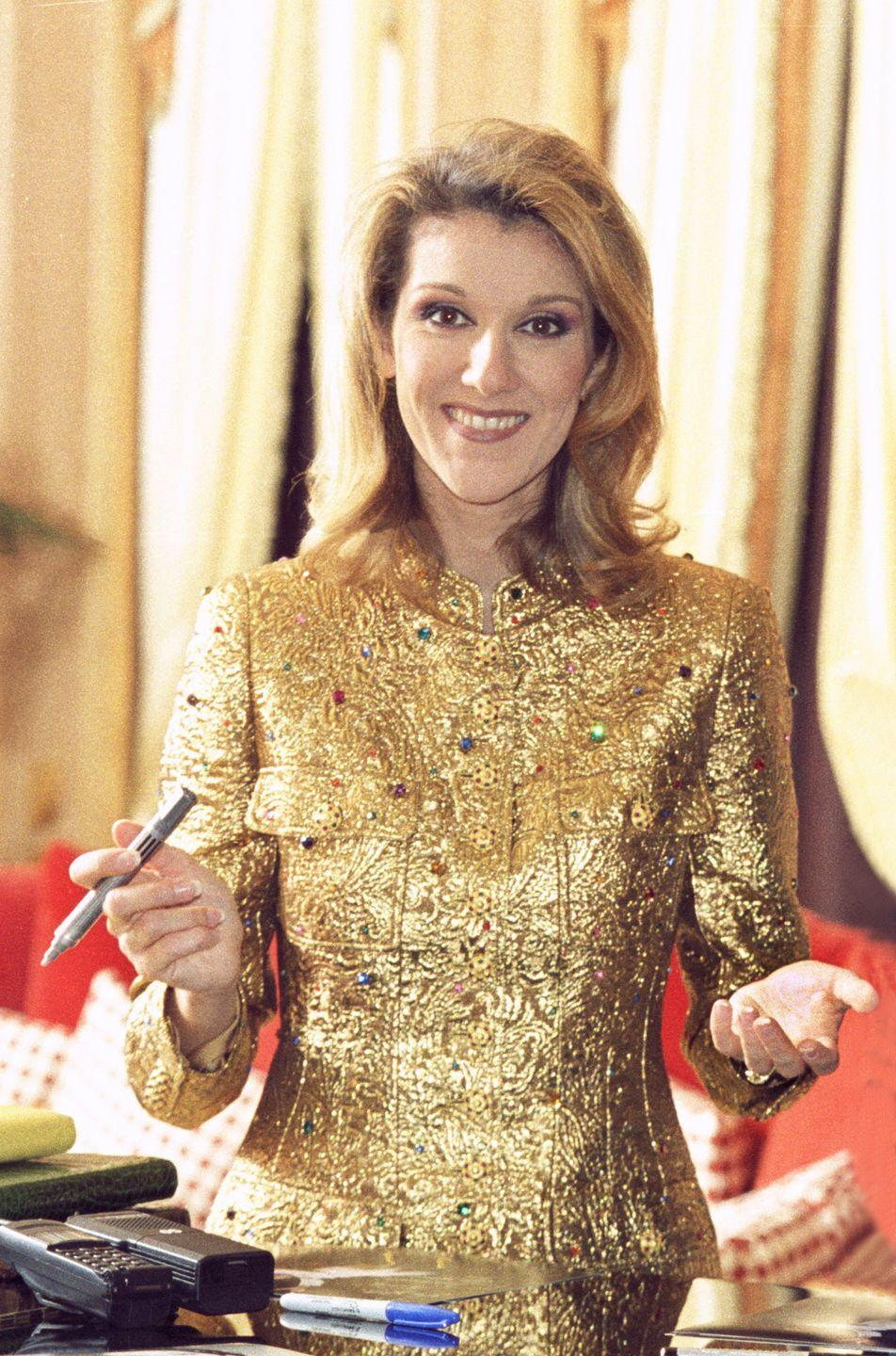 """<p>You know what they say: """"Life imitates art."""" Dion looked like magnificent masterpiece in this structured gold blazer. If the blazer itself wasn't enough, the designer added multicolored gems as a final touch. </p>"""