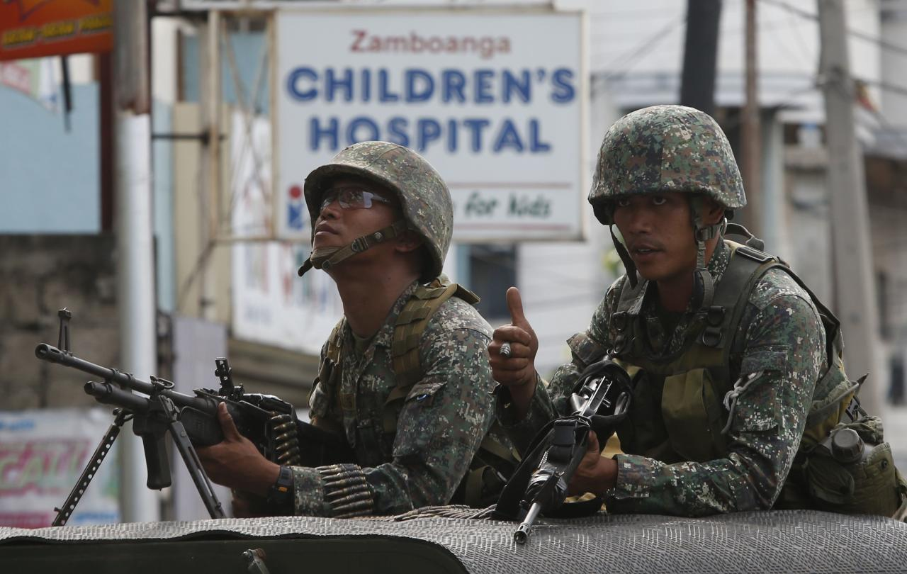 Members of the Philippine marines hold their weapons aboard a truck as they block a road during fighting between government soldiers and Muslim rebels of Moro National Liberation Front (MNLF) in Zamboanga city, southern Philippines, September 15, 2013. A week of violence in the southern Philippines has undercut hopes of lasting peace in the resource-rich region and exposed the government to criticism for underestimating rogue Muslim rebels who feel ignored by a landmark deal last year. REUTERS/Erik De Castro (PHILIPPINES - Tags: CIVIL UNREST CONFLICT POLITICS)