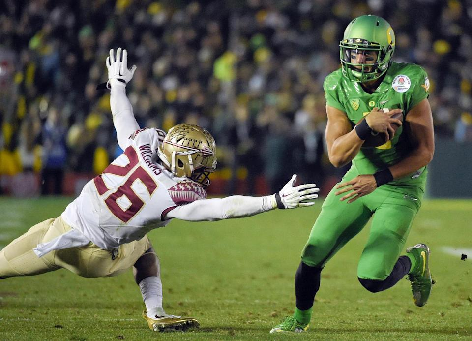 Oregon quarterback Marcus Mariota, right, scores past Florida State defensive back P.J. Williams during the second half of the Rose Bowl NCAA college football playoff semifinal, Thursday, Jan. 1, 2015, in Pasadena, Calif. (AP Photo/Mark J. Terrill)