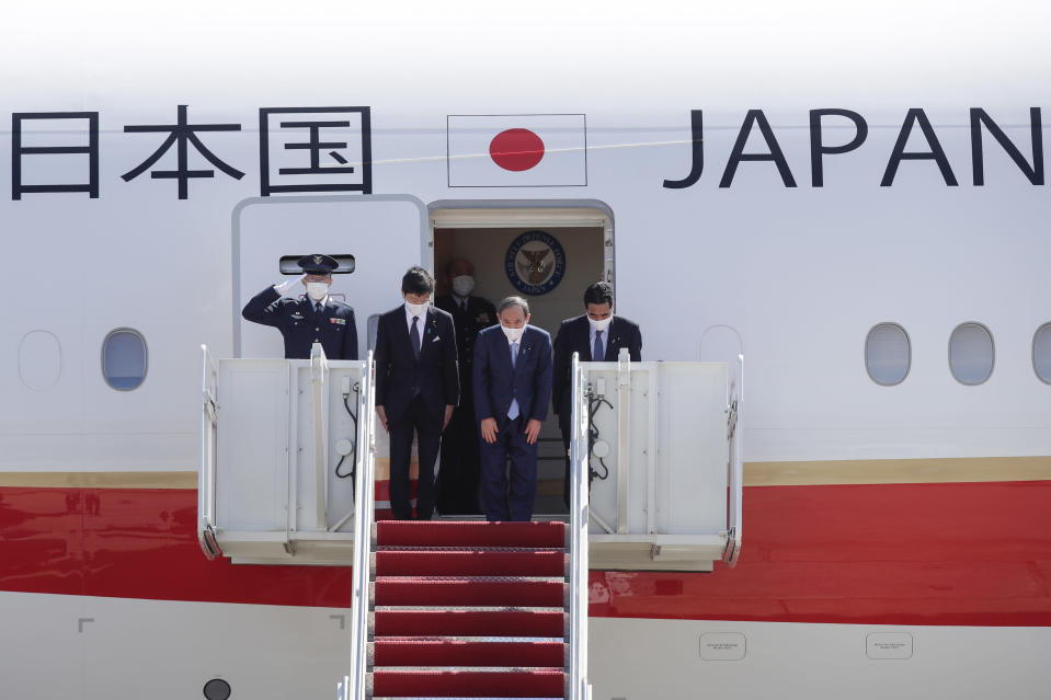 Japanese Prime Minister Yoshihide Suga boards his plane to depart at Andrews Air Force Base, Md., Saturday, April 17, 2021, after his visit to Washington. (AP Photo/Luis M. Alvarez)