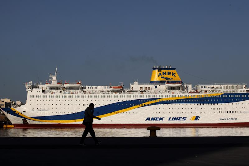 A man walks in front of a docked ship at the port of Piraeus near Athens, during a 24-hour nationwide general strike on Thursday, Oct. 18, 2012. Labor unions in recession-hobbled Greece are holding another general strike against a new harsh austerity program, as European leaders beset by a deep debt crisis and economic stagnation gather for a summit meeting in Brussels. (AP Photo/Petros Giannakouris)