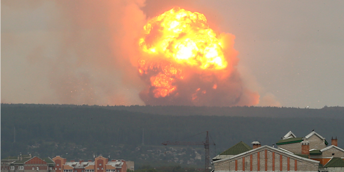 A view shows flame and smoke rising from the site of blasts at an ammunition depot in Krasnoyarsk region