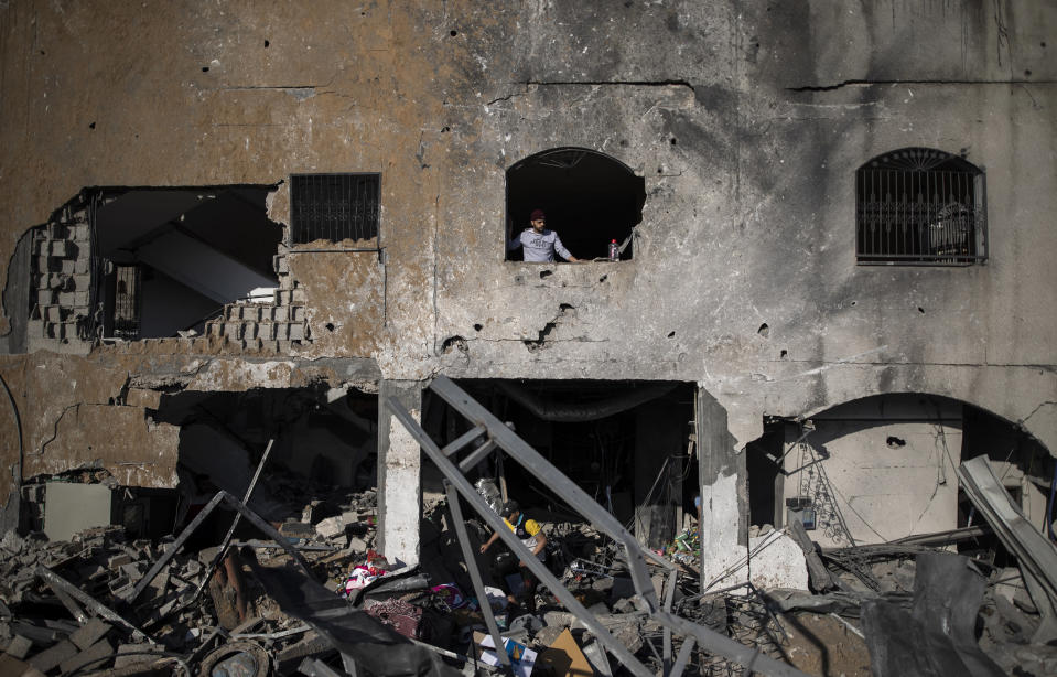 Palestinians inspect their destroyed home after being hit by Israeli airstrikes in town of Beit Lahiya, northern Gaza Strip, Thursday, May 13, 2021. Gaza braced for more Israeli airstrikes and communal violence raged across Israel after weeks of protests and violence in Jerusalem. (AP Photo/Khalil Hamra)