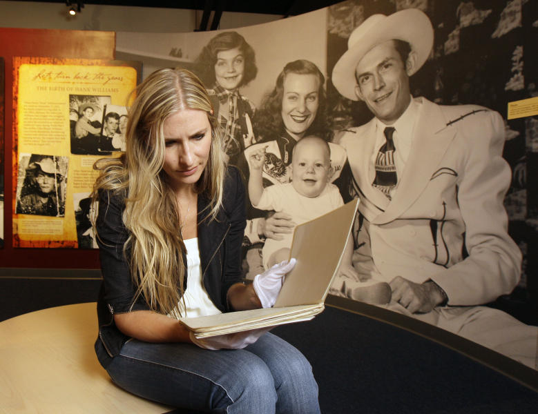 """In an Aug. 18, 2011 photo, Holly Williams, granddaughter of country music pioneer Hank Williams, looking through a notebook of her grandfather's song lyrics at the Country Music Hall of Fame and Museum in Nashville, Tenn.  Holly Williams is one of the performers on """"The Lost Notebooks of Hank Williams,"""" a collection of his unfinished lyrics put to music. (AP Photo/Mark Humphrey)"""