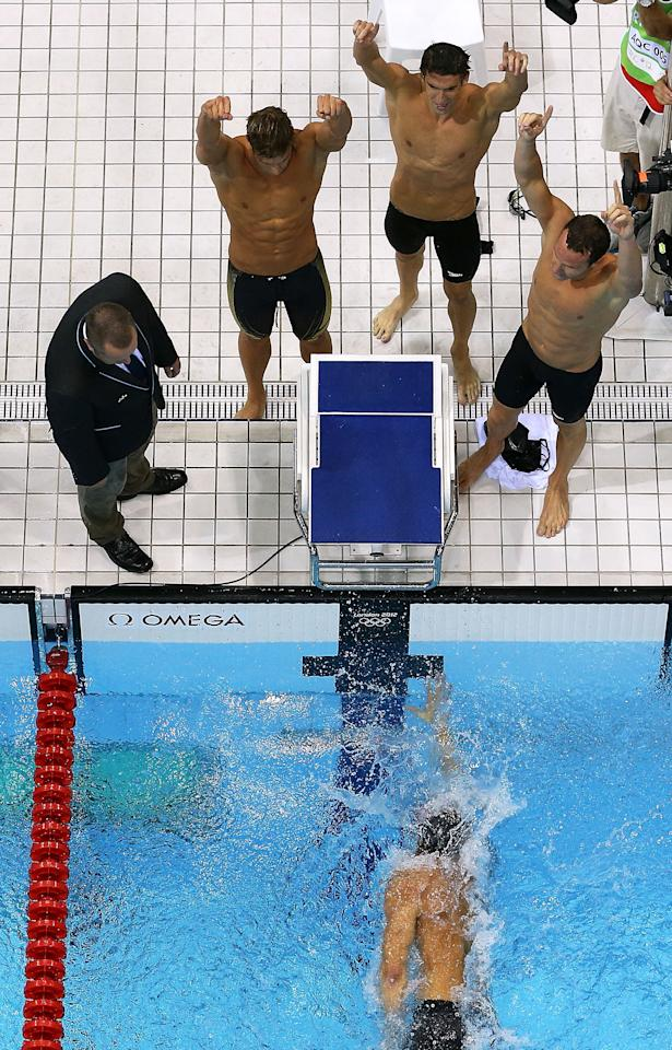 LONDON, ENGLAND - AUGUST 04:  Matthew Grevers, Brendan Hansen, and Michael Phelps of the United States cheer on team mate Nathan Adrian as he finishes the Men's 4x100m Medley Relay on Day 8 of the London 2012 Olympic Games at the Aquatics Centre on August 4, 2012 in London, England.  (Photo by Chris McGrath/Getty Images)