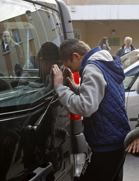 A youngster cries against a hearse, following a ceremony at the Ozar Hatorah Jewish school where a gunman opened fire killing four people in Toulouse, southwestern France, Tuesday, March 20, 2012. A father and his two sons were among four people who died Monday when a gunman opened fire in front of a Jewish school in a city in southwest France, the Toulouse prosecutor said Monday.(AP Photo/Remy de la Mauviniere)