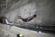 A youth dives into a drainage ditch alongside an unfinished, abandoned highway in Caracas, Venezuela, on Thursday, July 15, 2021. Residents directed tubes toward the drainage ditch to fill it with water coming from a nearby mountain in order to do laundry, bathe and collect water to take home, while children use it as a pool. (AP Photo/Ariana Cubillos)