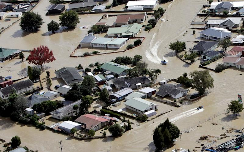 Jet boats drive through the flooded streets of the North Island town of Edgecumbe in New Zealand - Credit: Andrew Warner/AP