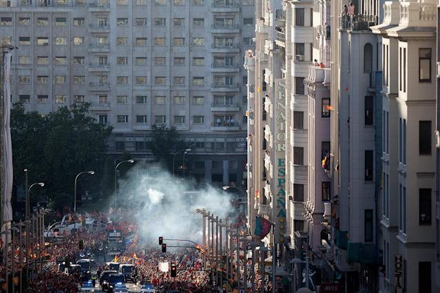MADRID, SPAIN - JULY 02: Smoke from flares dissipates over a crowd of supporters as the Spain team celebrates with the UEFA EURO 2012 trophy on a double-decker bus during the Spanish team's victory parade on July 2, 2012 in Madrid, Spain. Spain beat Italy 4-0 in the UEFA EURO 2012 final match in Kiev, Ukraine, on July 1, 2012. (Photo by Pablo Blazquez Dominguez/Getty Images)