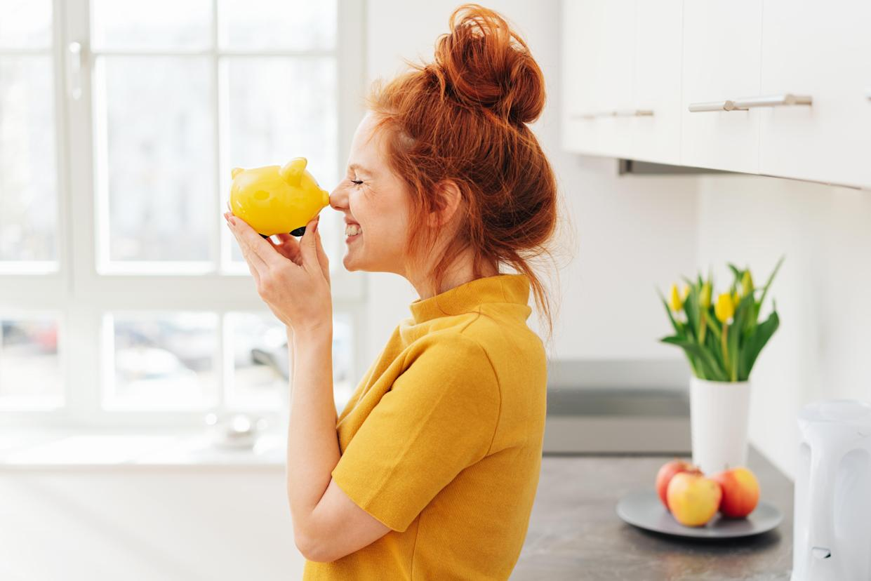 Smiling red-haired woman playing with yellow piggy bank in her hands, viewed from the side in bright room interior. Money savings concept