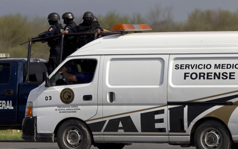 Federal police stand guard on a vehicle behind a forensic truck containing bodies found on the highway connecting the northern Mexican metropolis of Monterrey to the U.S. border, along the Reynosa-Cadereyta road, in the town of San Juan near the city of Monterrey, Mexico, Sunday, May 13, 2012.  Authorities struggled on Monday to identify dozens of people found mutilated and scattered in a pool of blood in a region where Mexico's two dominant drug cartels are trying to outdo each other in bloodshed while warring over smuggling routes. (AP Photo/Christian Palma)