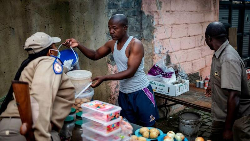 A Gauteng Traffic Police officer confiscates goods from an informal trading post during a mixed patrol of South African National Defence Force (SANDF) and Gauteng Traffic Police in Alexandra, Johannesburg, on March 31, 2020. -