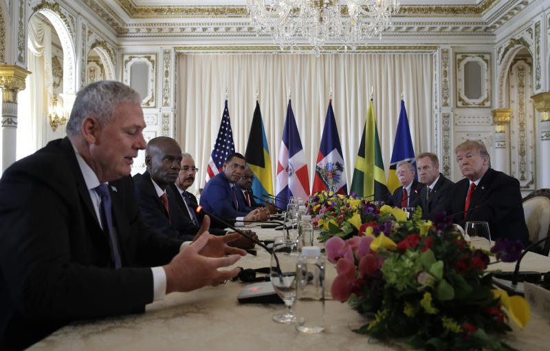 President Donald Trump, right, meets with Caribbean leaders at Mar-A Lago, Friday, March 22, 2019, in Palm Beach, Fla. From left are Saint Lucia's Prime Minister Allen Michael Chastanet, Haiti President Jovenel Moise,Dominican Republic President Danilo Medina, Jamaica Prime Minister Andrew Holness and Bahama Prime Minister Hubert Minnis. (AP Photo/Carolyn Kaster)