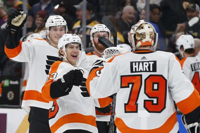 Philadelphia Flyers' Oskar Lindblom (23) and teammates celebrate with goalie Carter Hart (79) after defeating the Boston Bruins in a shootout during an NHL hockey game in Boston, Sunday, Nov. 10, 2019. (AP Photo/Michael Dwyer)