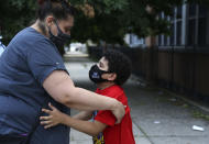 Christina Mendez leans down to hug her 7-year-old son, Elidios Kenel, after meeting with dozens of other concerned parents and students at St. Francis Xavier School in Newark, Thursday, Aug. 6, 2020. The Archdiocese of Newark announced the school's permanent closure the previous week. (AP Photo/Jessie Wardarski)