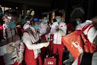 <p>Members of China's tennis table team disinfect their gloves as they arrive for the Tokyo 2020 Olympic Games at Narita International Airport in Narita, Chiba prefecture on July 17, 2021. (Photo by Charly TRIBALLEAU / AFP)</p>