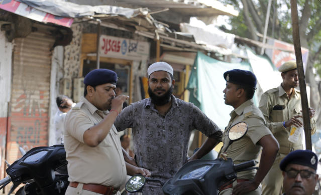 An Indian Muslim man interacts with policemen in Ahmadabad, India, Saturday, Nov. 9, 2019. India's Supreme Court has ruled in favor of a Hindu temple on a disputed religious ground and ordered that alternative land be given to Muslims. The dispute over land ownership has been one of the country's most contentious issues. (AP Photo/Ajit Solanki)