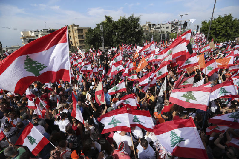 Supporters of Lebanese President Michel Aoun hold Free Patriotic Movement Party and Lebanese flags during a protest near the presidential palace in the Beirut suburb of Baabda, Lebanon, Sunday, Nov. 3, 2019. Thousands of people are marching to show their support for Aoun and his proposed political reforms that come after more than two weeks of widespread anti-government demonstrations. (AP Photo/Hassan Ammar)