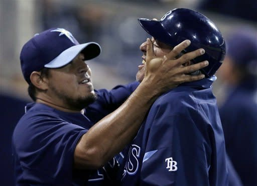 Tampa Bay Rays relief pitcher Joel Peralta, left, jokes third base coach Tom Foley in the dugout after the eighth inning of an exhibition spring training baseball game against the Pittsburgh Pirates in Port Charlotte, Fla., Monday, March 25, 2013. (AP Photo/Elise Amendola)