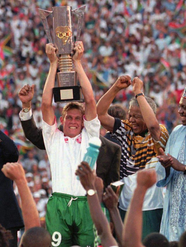 "FILE - In this Feb. 3, 1996 file photo, South Africa's captain Neil Tovey hoists the African Nations Cup trophy in the air after it was presented to him by President Nelson Mandela, right, following South Africa's 2-0 win over Tunisia in the final match in Johannesburg. ""Sport can create hope, where once there was only despair. It is more powerful than governments in breaking down racial barriers. It laughs in the face of all types of discrimination,"" Mandela said. South Africa's President Jacob Zuma said, Thursday, Dec. 5, 2013, that Mandela has died. He was 95. (AP Photo/Cobus Bodenstein, File)"