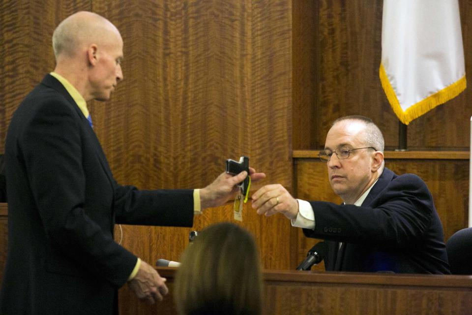 Prosecutor William McCauley (L) reviews a .22 caliber gun with State Police ballistics expert John Conroy during the murder trial of former NFL player Aaron Hernandez at the Bristol County Superior Court in Fall River, Massachusetts, February 23, 2015. Hernandez is charged with the 2013 murder of Odin Lloyd, 27, a semiprofessional football player who had been dating the sister of Hernandez's fiancee. REUTERS/Dominick Reuter/Pool (UNITED STATES)