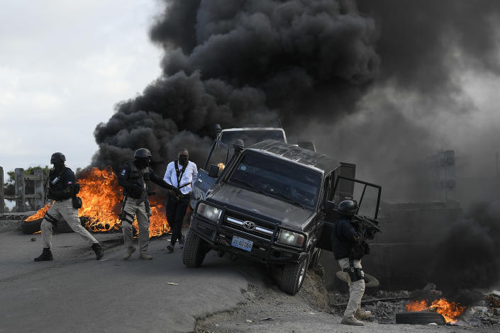 Police abandon their vehicle during a demonstration that turned violent in which protesters demanded justice for the assassinated President Jovenel Moise in Cap-Haitien, Haiti, Thursday, July 22, 2021. Demonstrations after a memorial service for Moise turned violent on Thursday afternoon with protesters shooting into the air, throwing rocks and overturning heavy concrete barricades next to the seashore as businesses closed and people took cover. (AP Photo/Matias Delacroix)