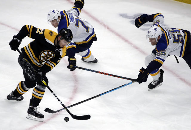 Boston Bruins left wing Peter Cehlarik (22) competes for the puck with St. Louis Blues center Oskar Sundqvist (70) and defenseman Colton Parayko (55) during the first period of an NHL hockey game Thursday, Jan. 17, 2019, in Boston. (AP Photo/Elise Amendola)