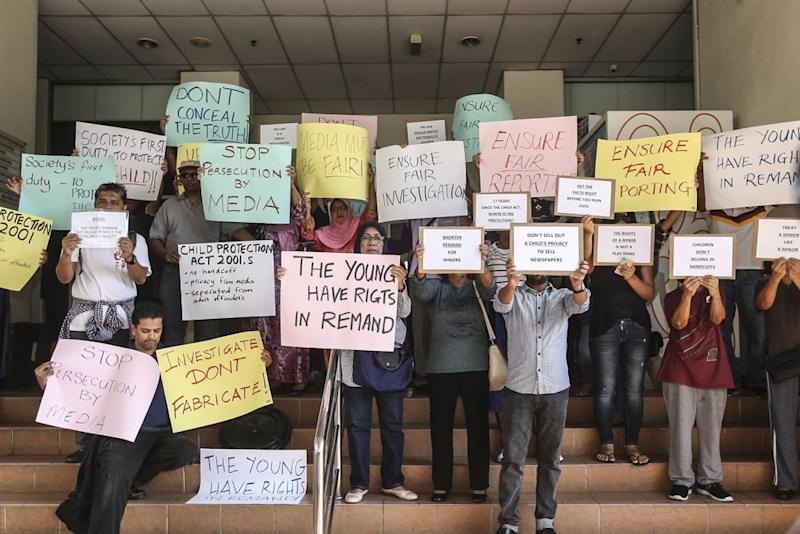 Demonstrators hold up placards demanding justice for the two stepsons of Nazrin Hassan, who are under a seven-day remand, at the lobby of the Petaling Jaya Majistrate's Court September 10, 2018. — Picture by Azneal Ishak