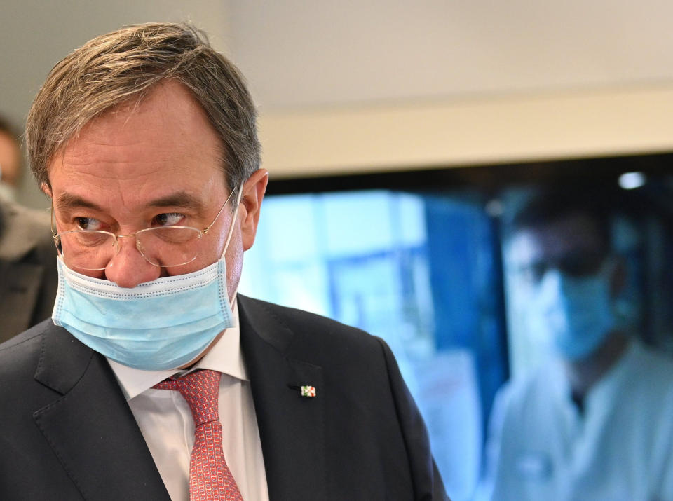 30 March 2020, North Rhine-Westphalia, Aachen: Armin Laschet (CDU), Prime Minister of North Rhine-Westphalia, who is wearing a face mask due to the corona pandemic, follows a treatment in an affiliated hospital during a press meeting at the start of the virtual hospital at the University Hospital RWTH Aachen. Photo: Henning Kaiser/dpa (Photo by Henning Kaiser/picture alliance via Getty Images)