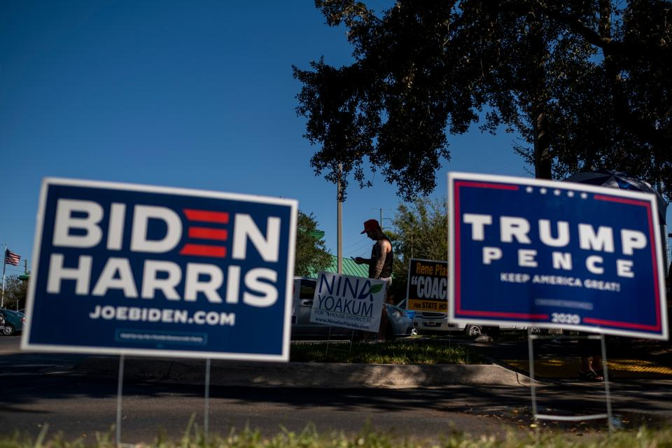 Biden and Trump campaign signs are displayed as voters line-up to cast their ballots during early voting at the Alafaya Branch Library in Orlando, Florida, on October 30, 2020. - Trump and Biden are focusing their greatest efforts on traditional battlegrounds that will decide the election -- such as Florida, where both campaigned this week. (Photo by Ricardo ARDUENGO / AFP) (Photo by RICARDO ARDUENGO/AFP via Getty Images)