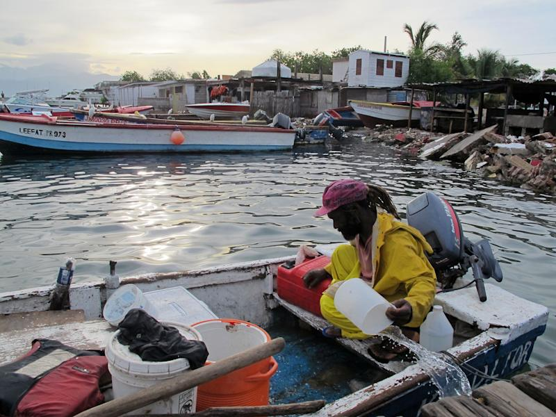Fisherman Daniel Edwards bails his small wooden skiff out in Port Royal, a fishing village just outside of Kingston, Jamaica, Sunday Aug. 5, 2012. Tropical Storm Ernesto is pushing for a brush with Jamaica on Sunday. (AP photo/David McFadden)