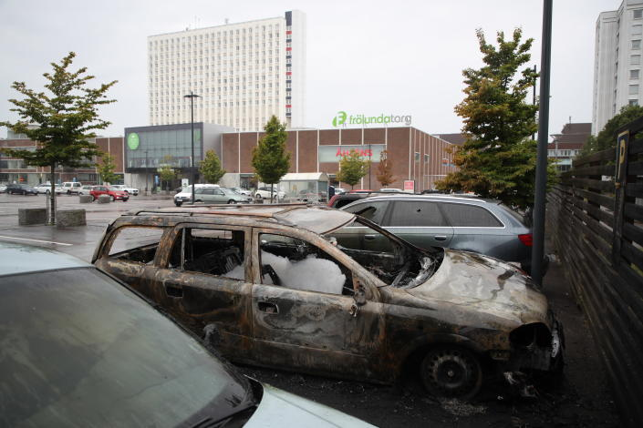 """Burned cars parked at Frolunda Square in Gothenburg, Tuesday, Aug. 14, 2018. Masked youth torched dozens of cars overnight in Sweden and threw rocks at police, prompting an angry response from the prime minister, who on Tuesday spoke of an """"extremely organized"""" night of vandalism. (Adam Ihse/TT via AP)"""