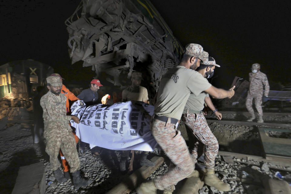 Soldiers and a rescue worker carry the body of a victim after receiving it from the wreckage at the site of a train collision in the Ghotki district, southern Pakistan, Monday, June 7, 2021. An express train barreled into another that had derailed in Pakistan before dawn Monday, killing dozens of passengers, authorities said. More than 100 were injured, and rescuers and villagers worked throughout the day to search crumpled cars for survivors and the dead. (AP Photo/Fareed Khan)
