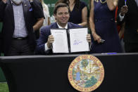 FILE - Florida Gov. Ron DeSantis holds up a just signed bill which would allow college athletes in the state to earn money from endorsement deals, at the University of Miami in Coral Gables, Fla., in this Friday, June 12, 2020, file photo. The NCAA Board of Directors is expected to greenlight one of the biggest changes in the history of college athletics when it clears the way for athletes to start earning money based on their fame and celebrity without fear of endangering their eligibility or putting their school in jeopardy of violating amateurism rules that have stood for decades.(AP Photo/Lynne Sladky, File)