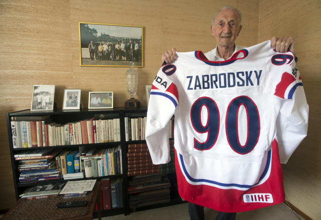 In this May 13, 2013 file photo former Czechoslovakian ice-hockey player Vladimir Zabrodsky, World Champion in 1947 and 1949, poses with his jersey in his home in Stockholm, Sweden. Zabrodsky died on Friday, March 20, 2020 at the age of 97 years. (Vit Simanek/CTK via AP)