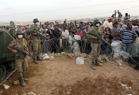 Turkish soldiers stand guard as Syrian Kurdish refugees wait behind the border fences to cross into Turkey near Suruc in Sanliurfa province